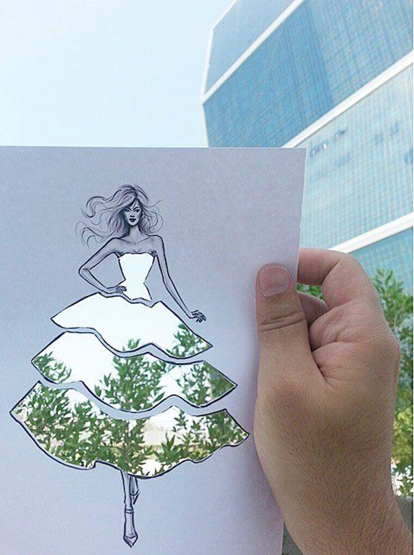 Ilustrator mody wykańcza swoje powycinane sukienki chmurami oraz budynkami